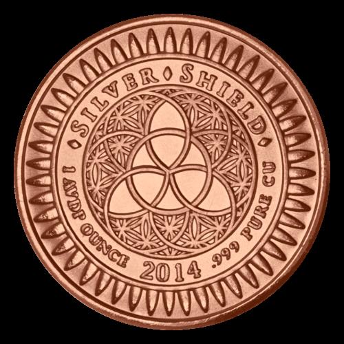 """Das revidierte Silver Shield Logo mit dem Trivium in der Mitte, eingekreist von den Worten """"Silver Shield 1 AVDP ounce 2014 .999 Pure CU"""" (Silver Shield 1 AVDP oz 2014 .999 reines KUPFER), umgeben von Kugeln."""